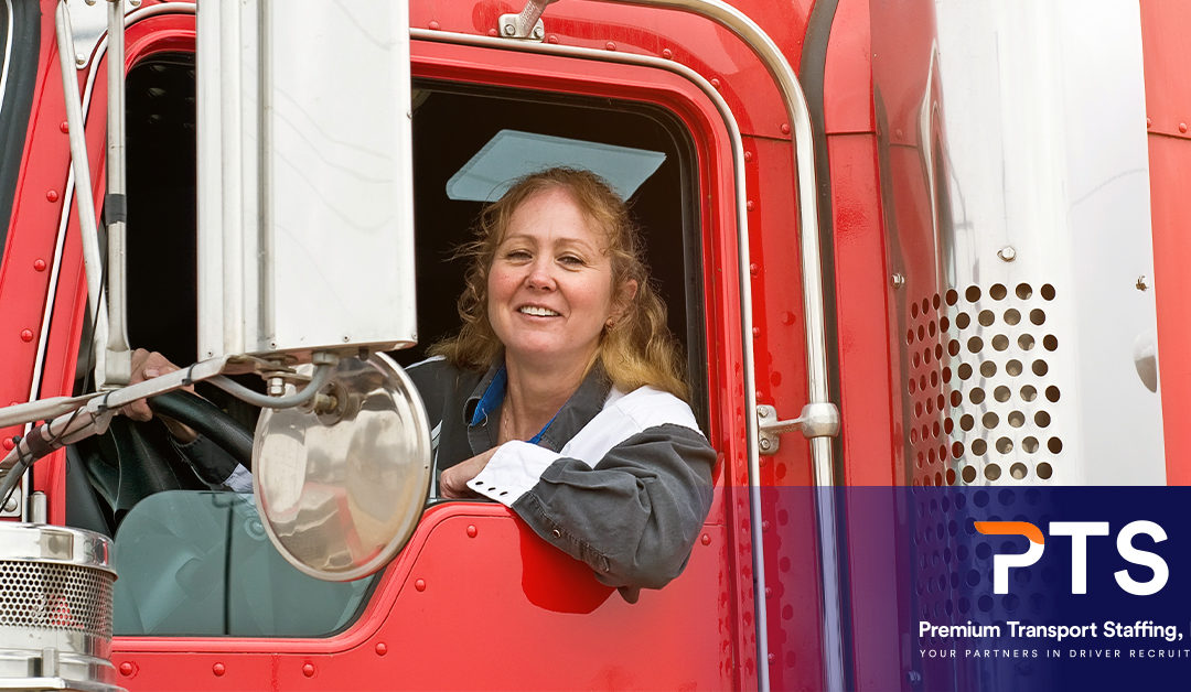 A happy female truck driver sitting in her truck and leaning out the window
