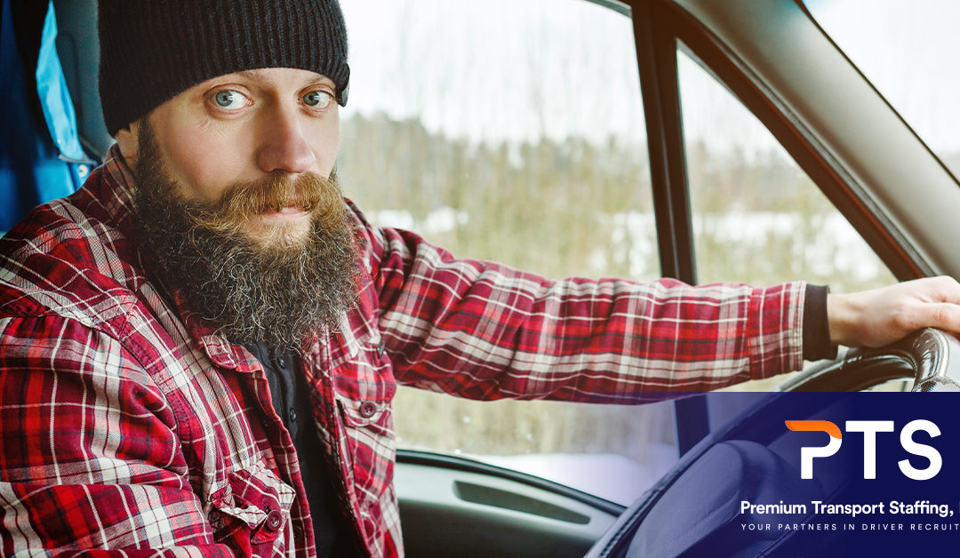 male driver in a truck dressed for cold weather