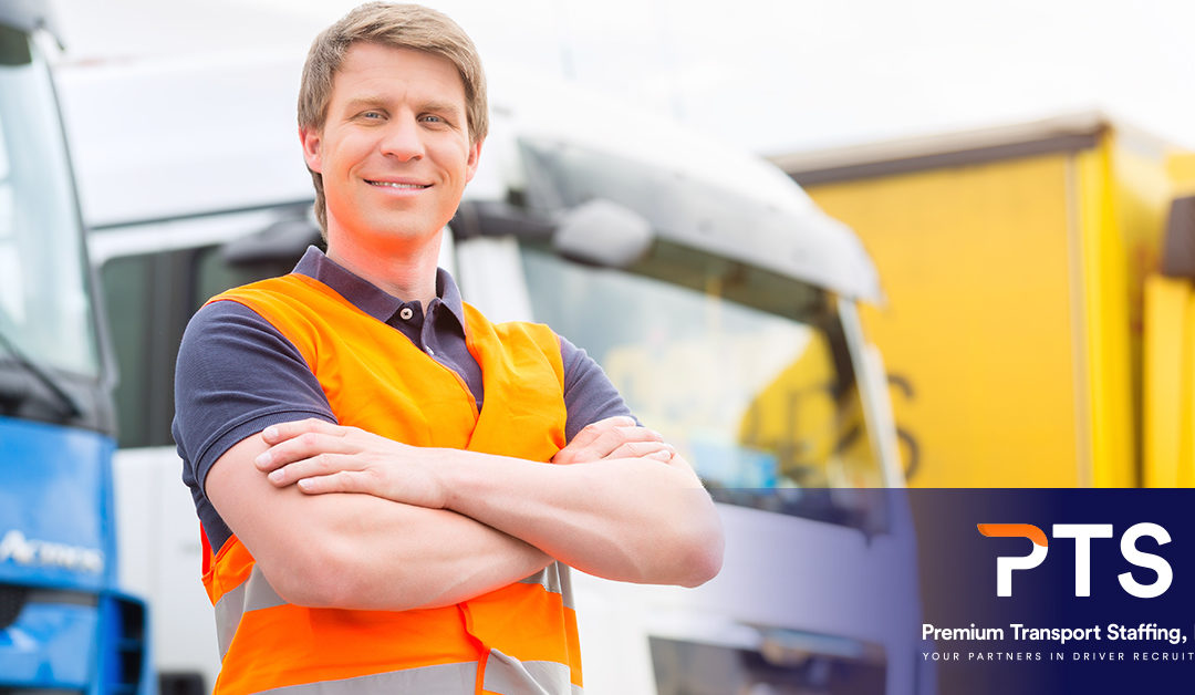 Smiling man wearing an orange vest and standing in front of a fleet of trucks