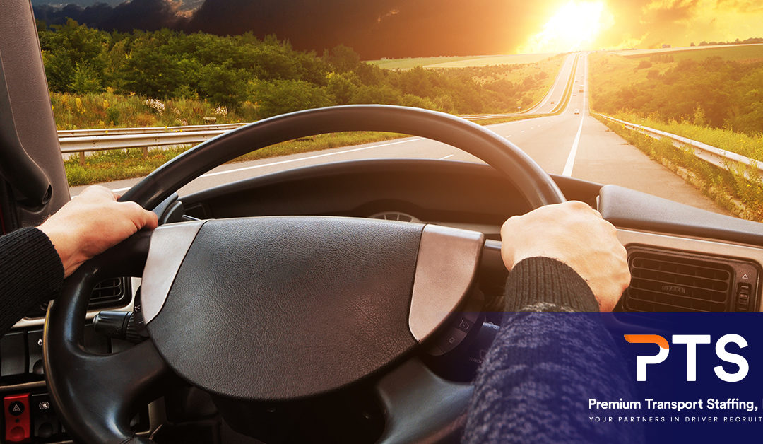 a close up of a driver's hands on the wheel, and the sun is rising ahead on the open road